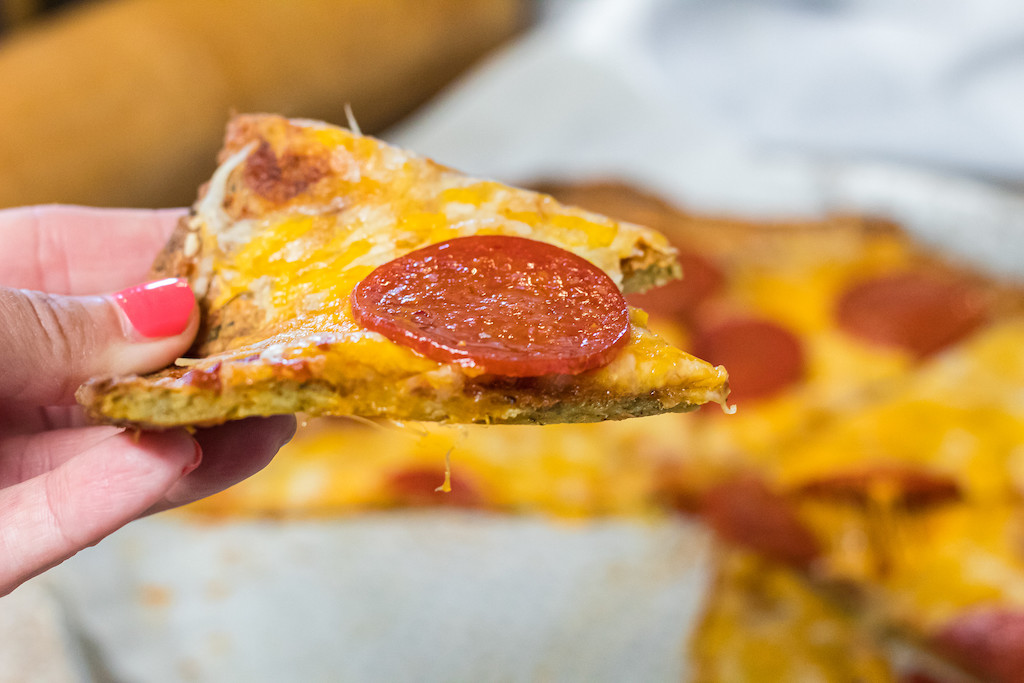 holding keto pork rind pizza slice with pepperoni and cheese