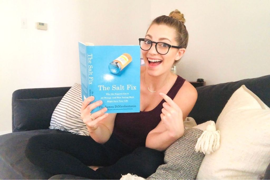 A woman sitting on a couch holding a book and pointing to it
