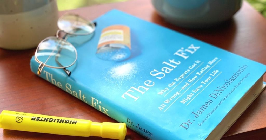 A book next to a highlighter on a table