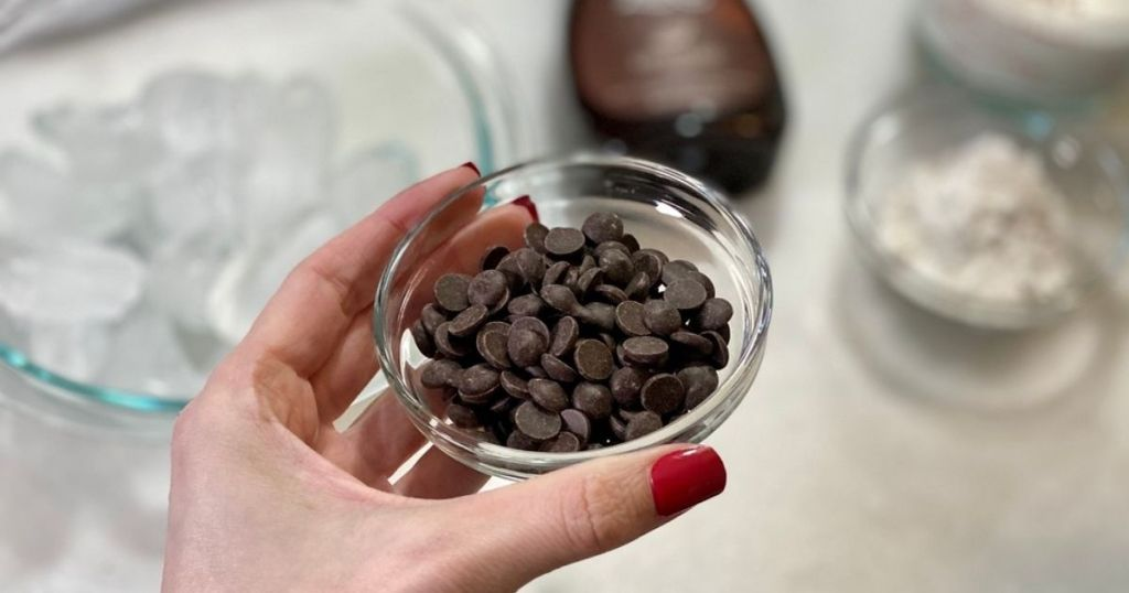 A hand holding a small bowl of chocolate chips