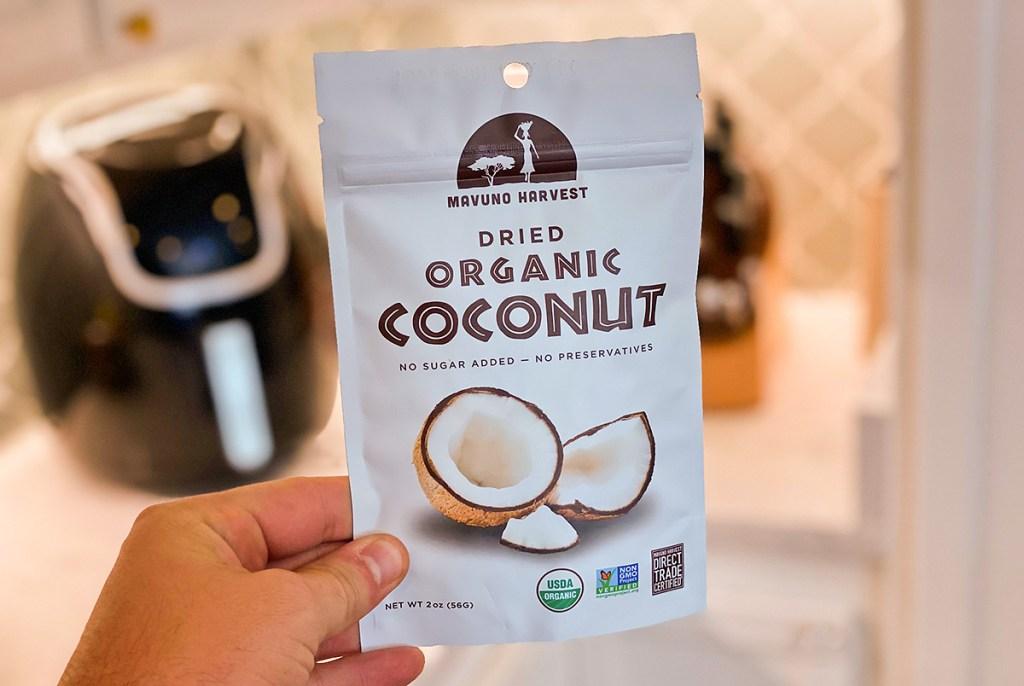 hand holding dried organic coconut bag