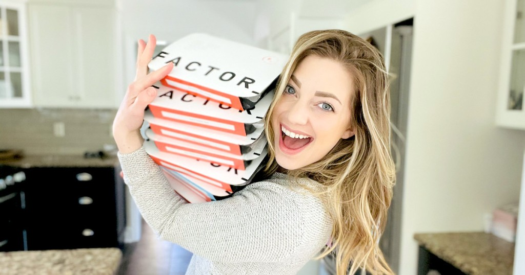 woman smiling holding a stack of factor meals