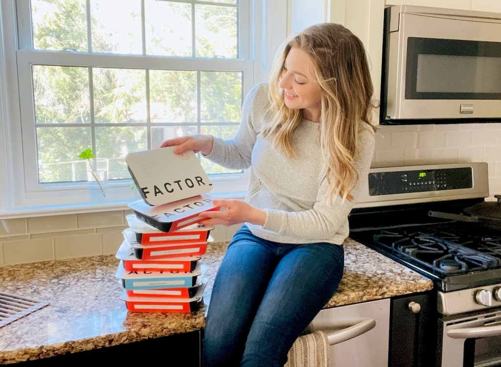 woman sitting on counter looking at stack of factor meals