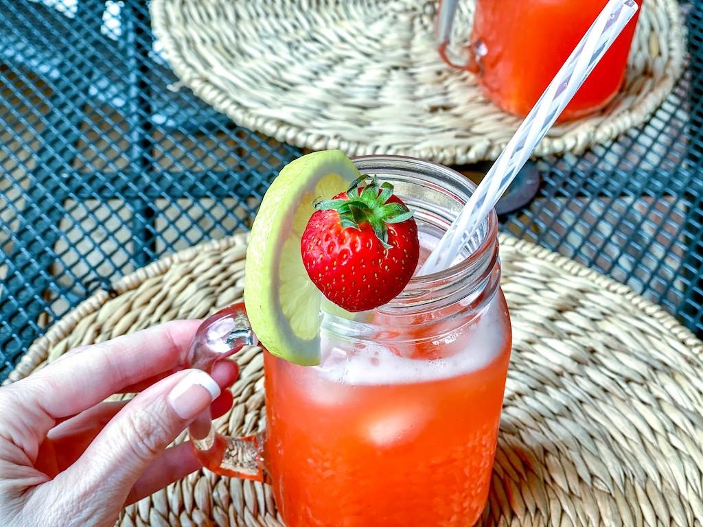 holding mason jar filled with keto strawberry lemonade