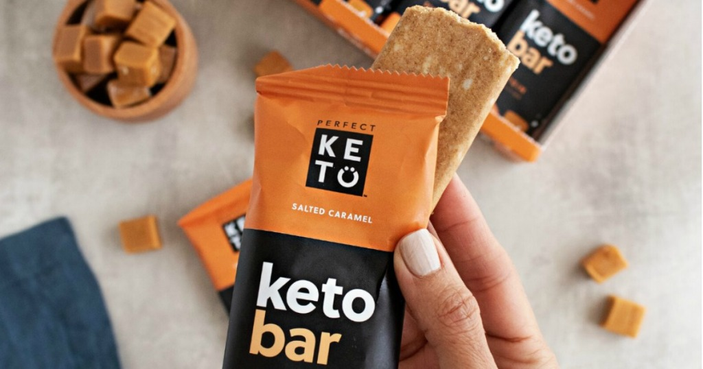 holding Perfect Keto salted caramel bar