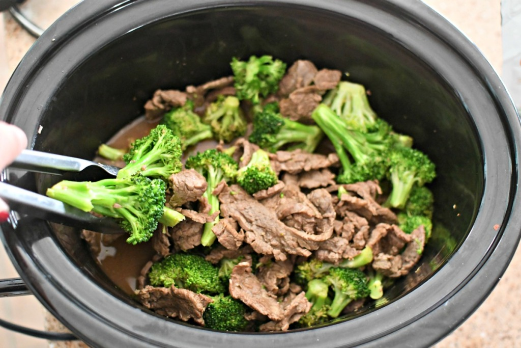 mixing keto beef and broccoli with tongs