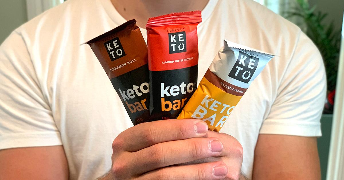 man holding 3 perfect keto bars