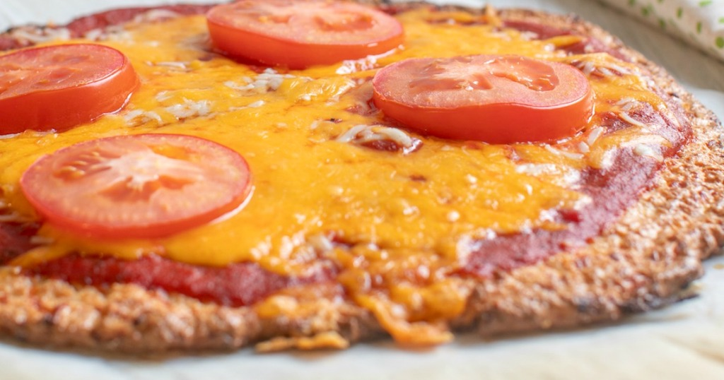 pork rind pizza crust with cheese and sliced tomatoes