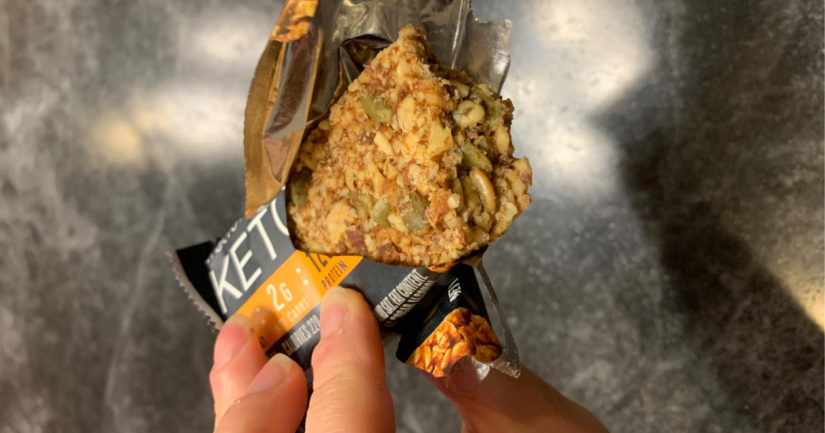 hand holding opened ratio keto protein bar