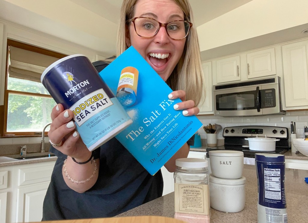 woman smiling holding the salt fix book with iodized jar of salt