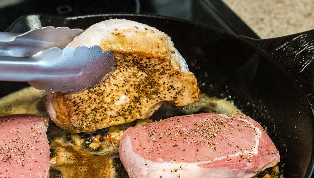 tongs holding seared pork chop in cast iron skillet
