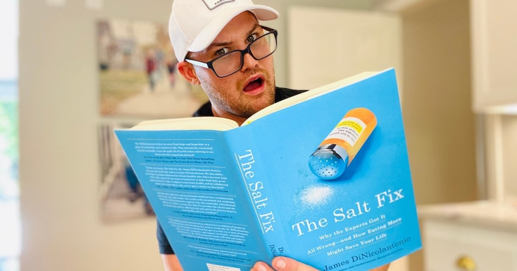 man wearing black glasses and white hat holding the salt fix book