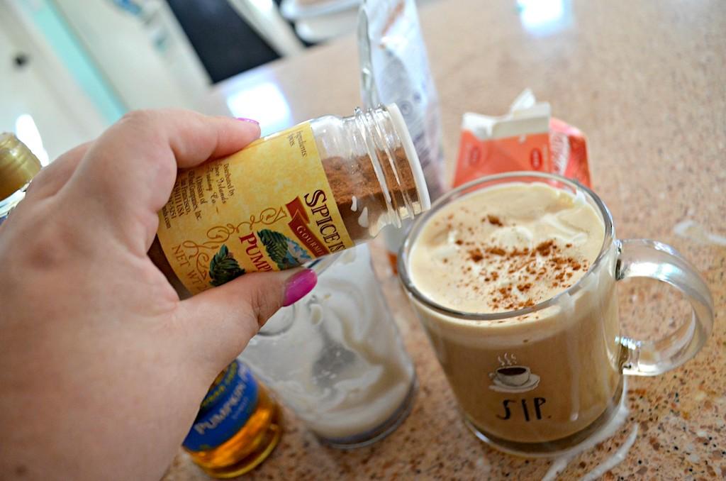 sprinkling pumpkin spice seasoning in latte