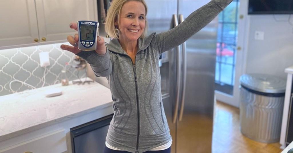 woman holding ketone blood meter