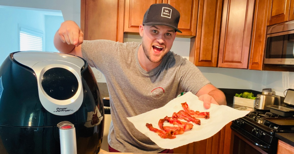 guy holding a plate of bacon