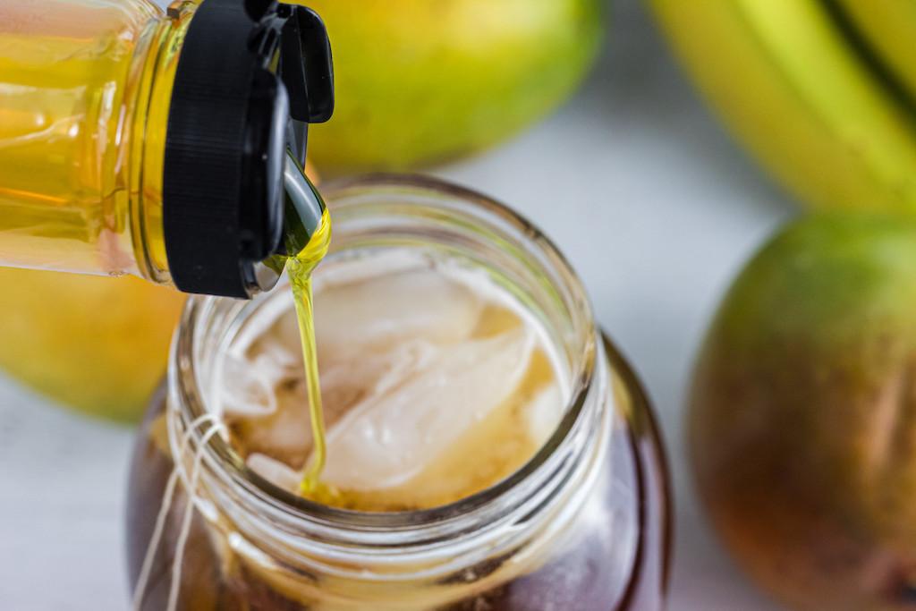 pouring ChocZero syrup into ice tea