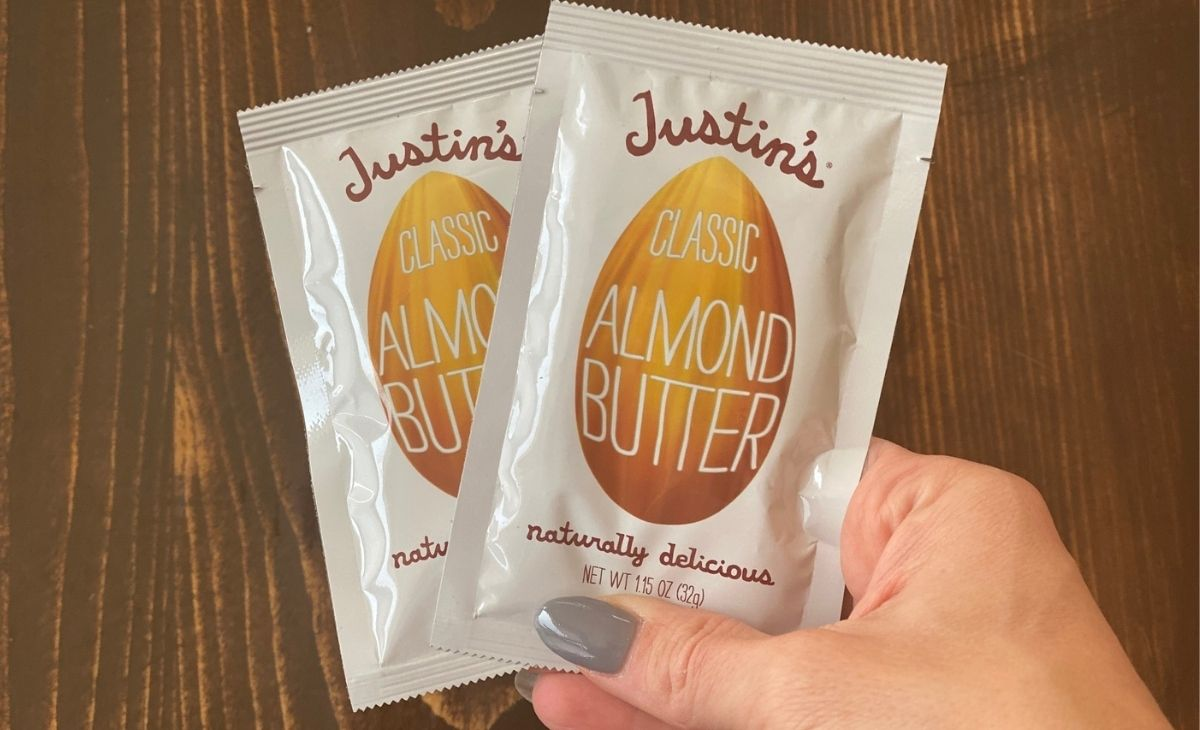 A hand holding two nut butter pouches
