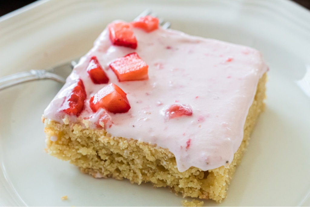 slice of keto almond cake with berry frosting