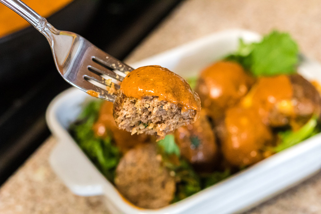 keto meatball on fork with pumpkin sauce