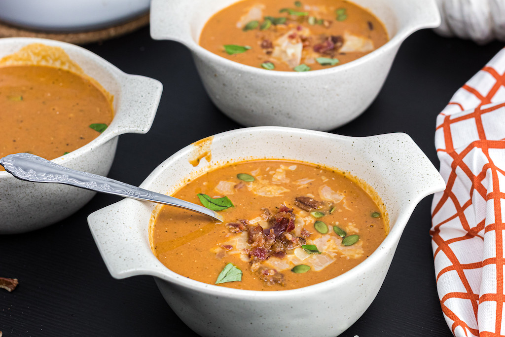 soup bowls filled with keto pumpkin soup and pumpkin seeds & bacon on top
