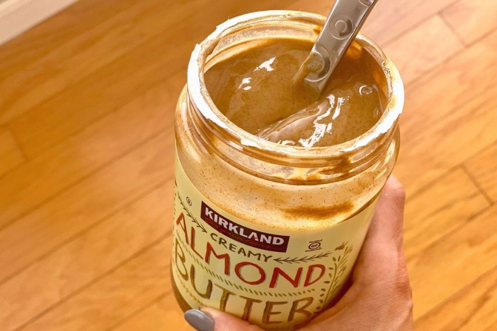 A hand holding a jar of open almond butter with a spoon in it