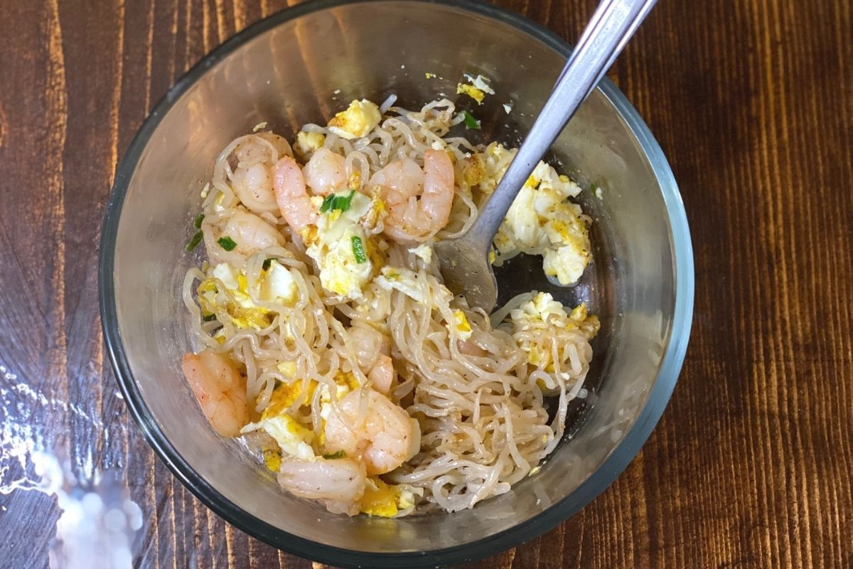 A ramen bowl with shrimp and egg on a table