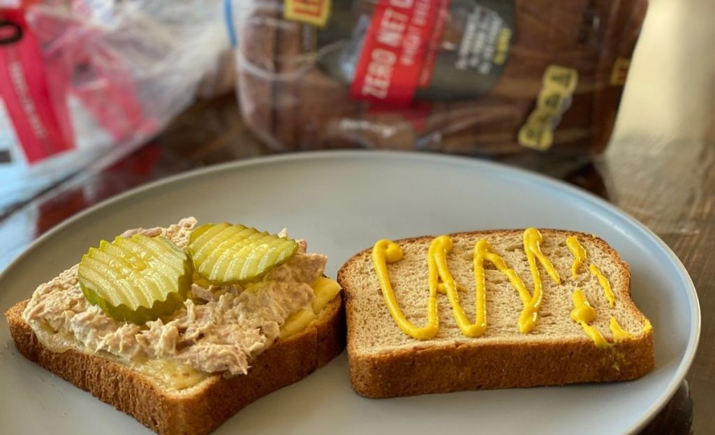 A tuna melt with pickles on a plate next to a loaf of bread