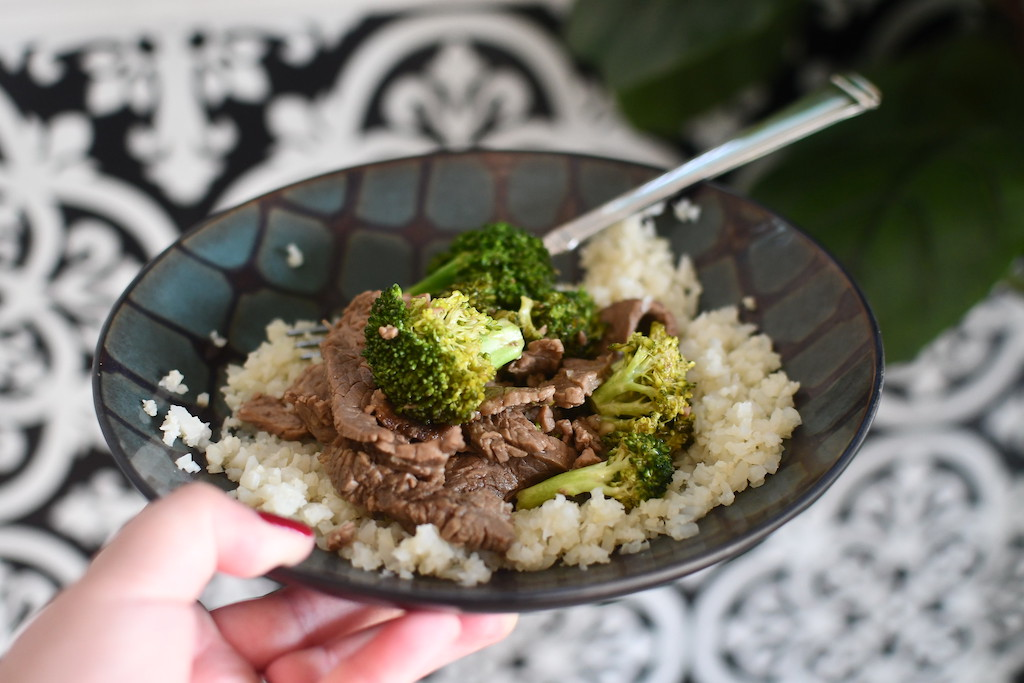 beef and broccoli in a bowl with cauliflower rice