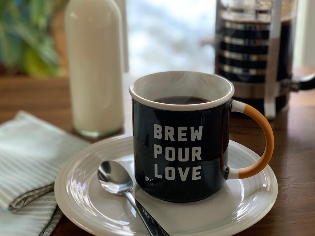 coffee mug on plate with black coffee