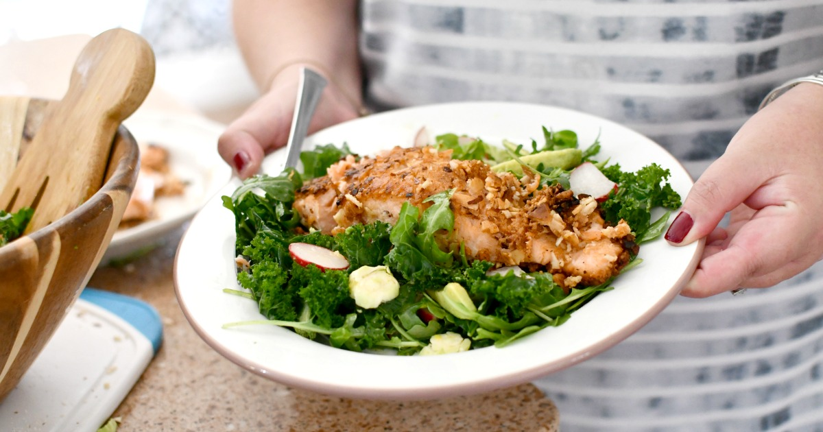 holding a plate of almond crusted salmon salad