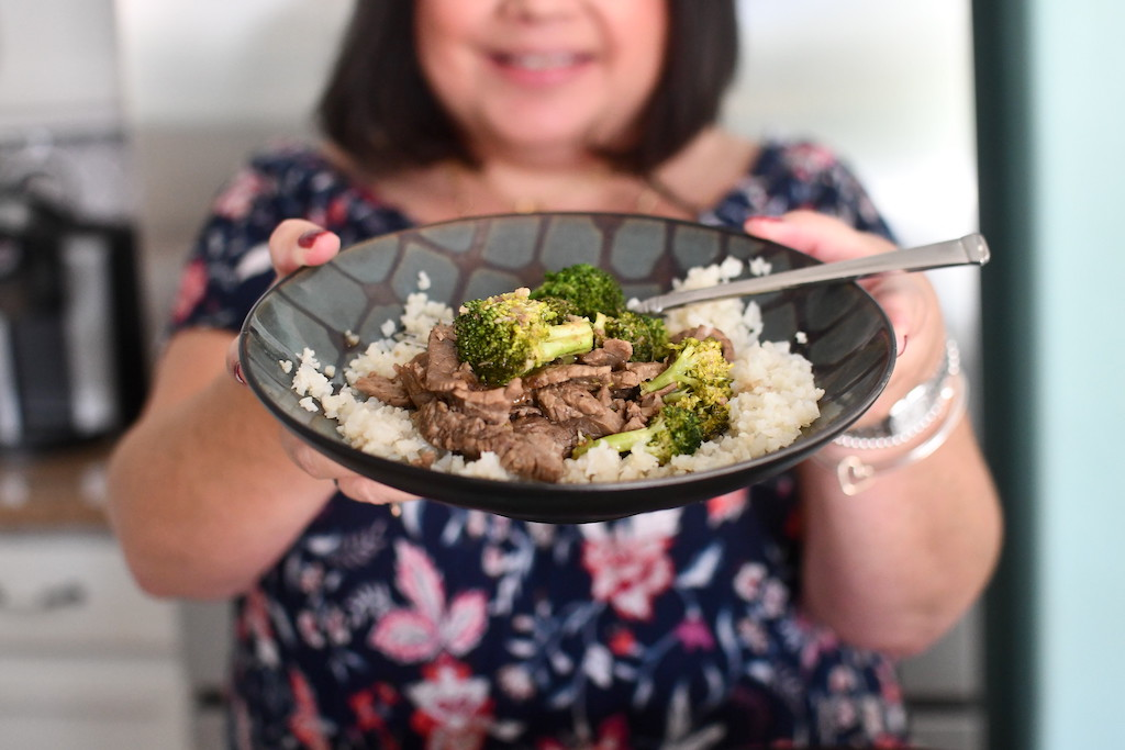 woman holding bowl of keto beef and broccoli