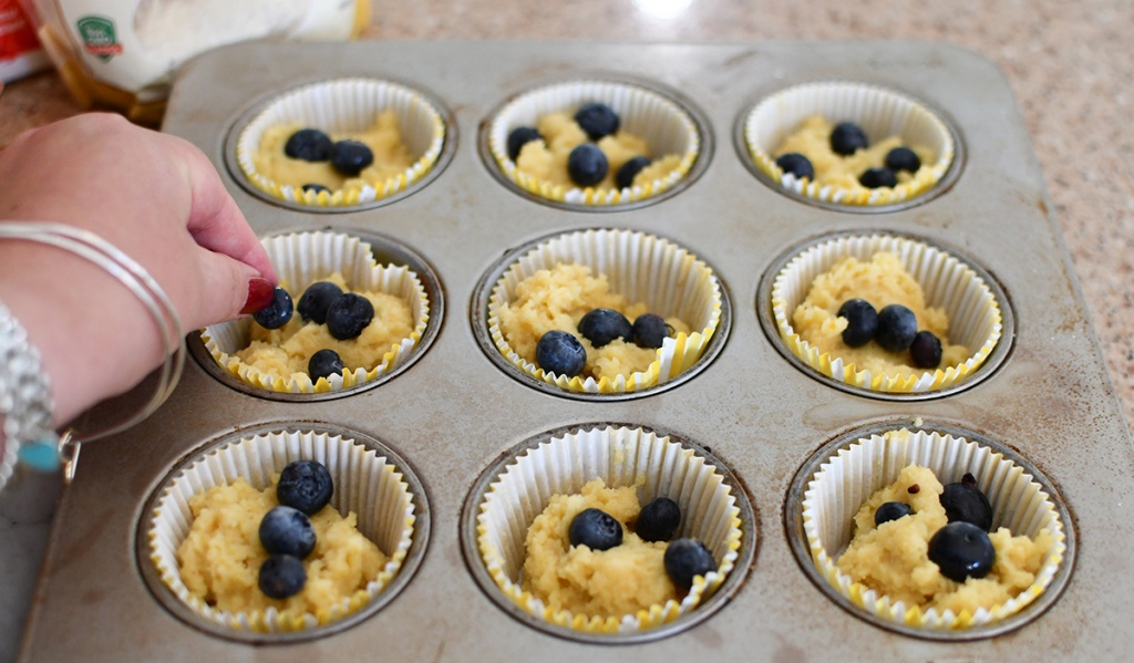 adding blueberries to muffin batter