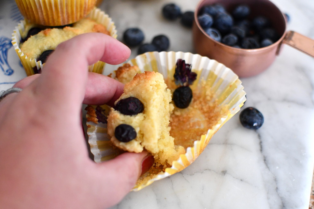 taking blueberry muffin out of cupcake liner