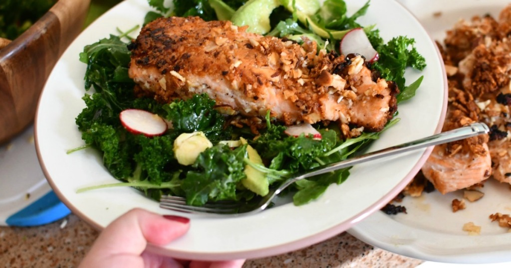 holding plate of keto salmon salad