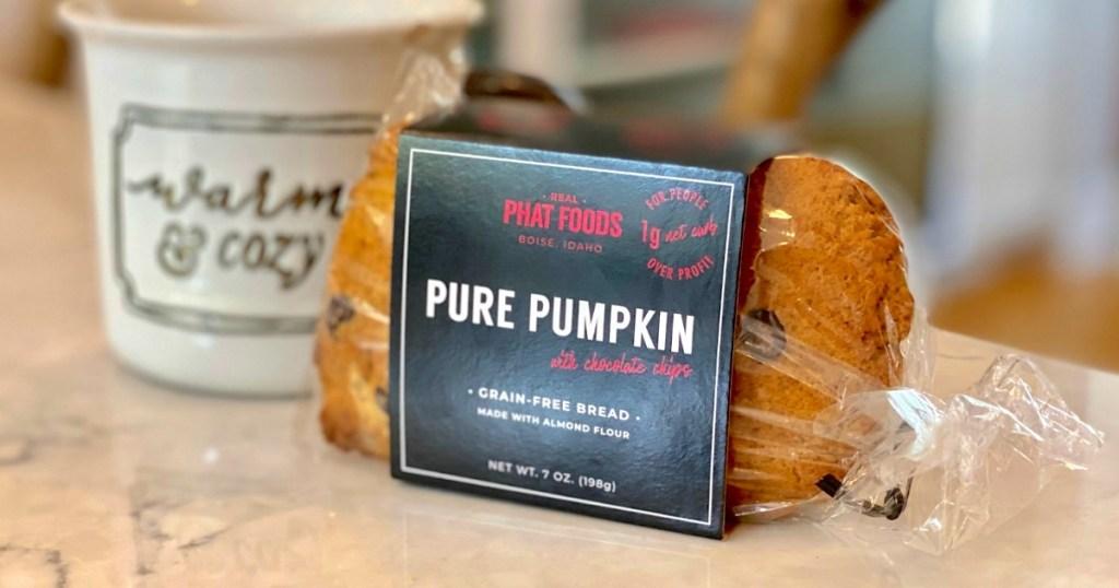 phat foods pumpkin bread sitting next to coffee mug