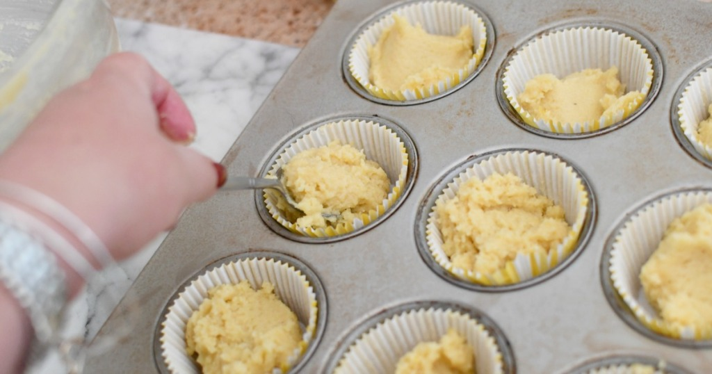 placing muffin batter into muffin tin