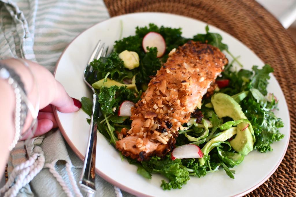 salad greens, avocado slices, and salmon on plate