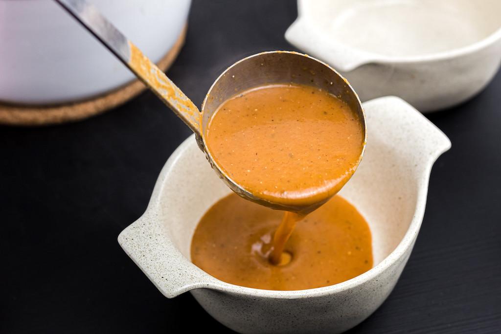 pouring keto pumpkin soup into bowl