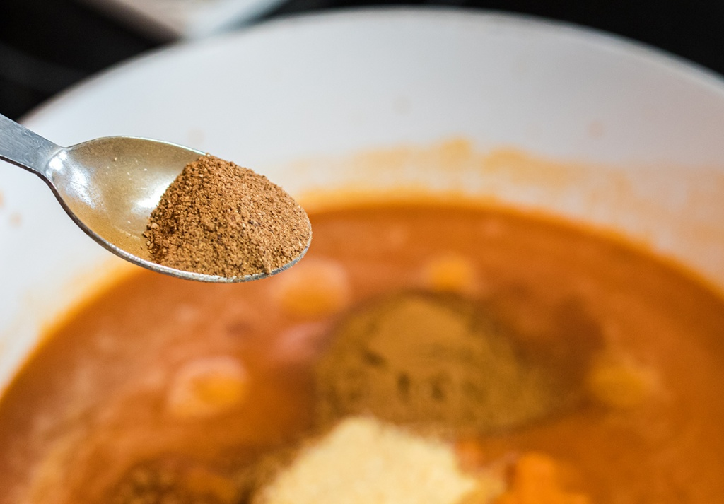 adding in spices to keto pumpkin soup