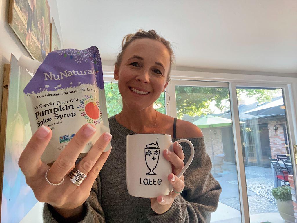 woman holding pumpkin spice syrup and latte mug