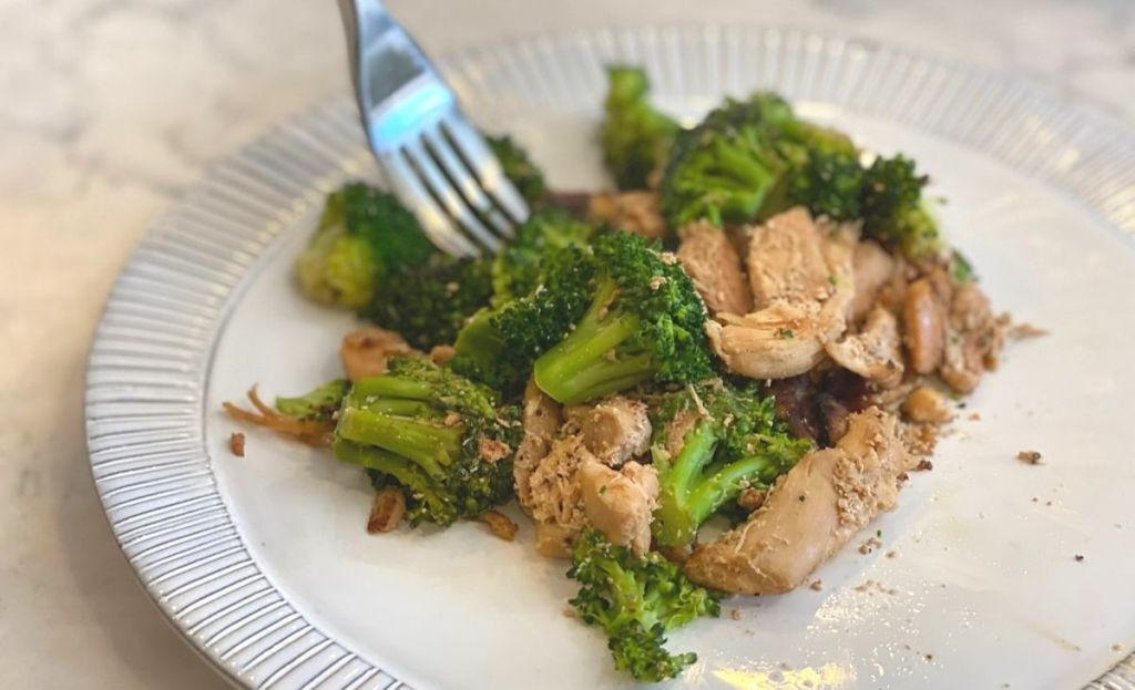 Broccoli and chicken on a plate with a fork