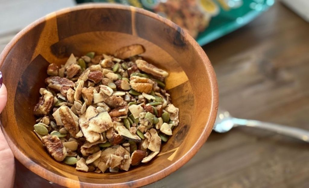 A bowl of granola next to a spoon on a table