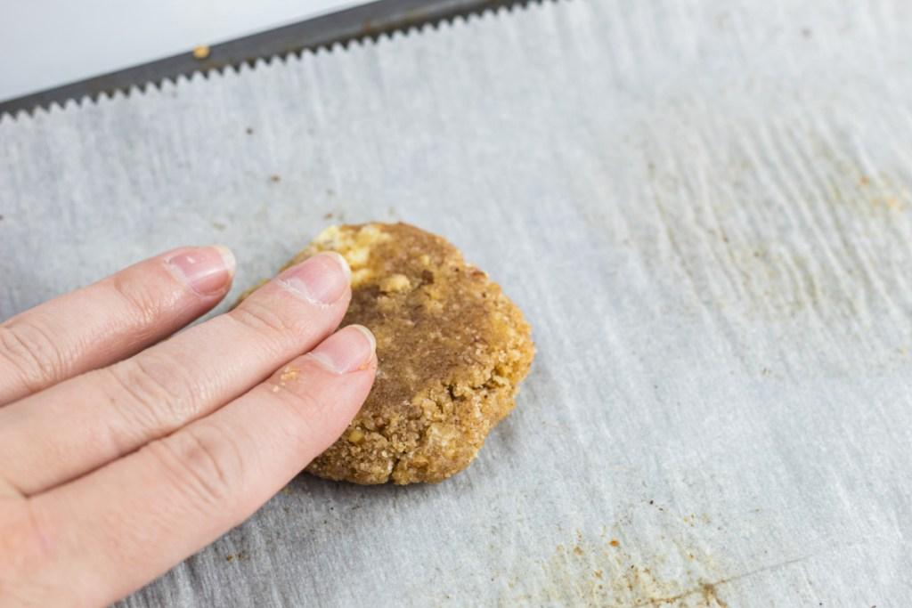 hand flattening cookie dough