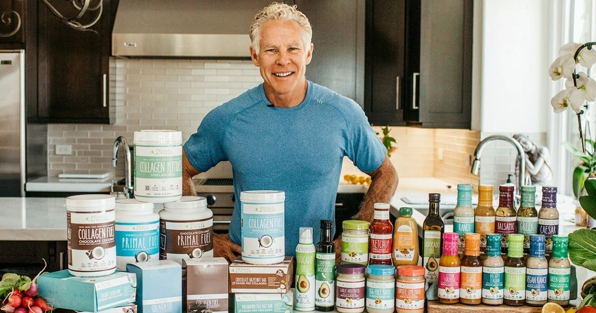A man in a kitchen with Primal Kitchen products on the counter