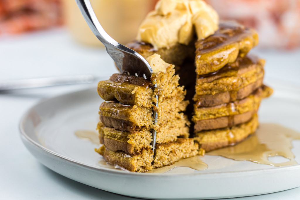 keto pumpkin chaffles stacked with fork taking large bite