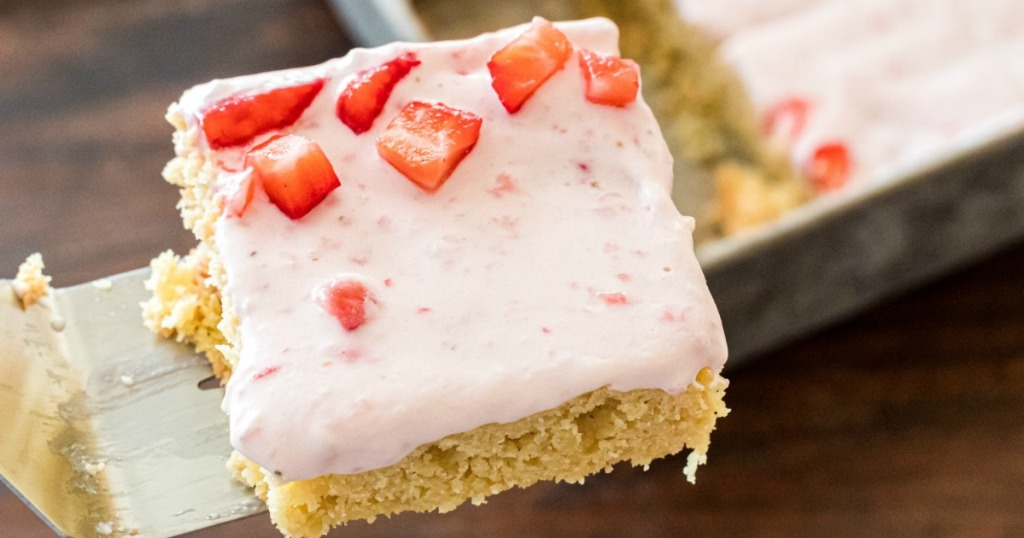 using spatula to pick up keto almond cake with strawberry frosting
