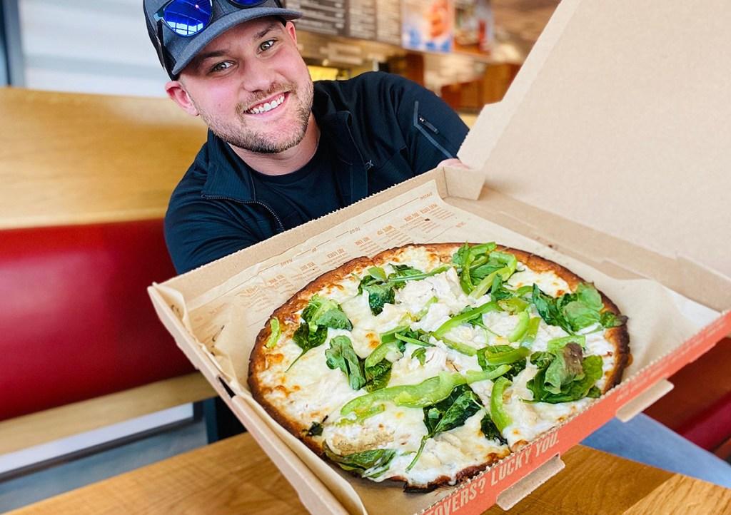 man holding blaze pizza