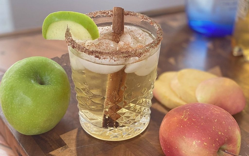 A caramel apple drink on a counter next to some apples