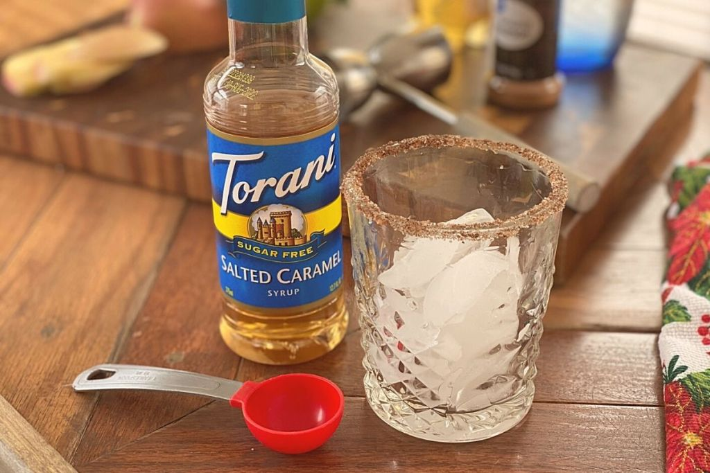 A glass of ice next to a measuring spoon and some flavored syrup