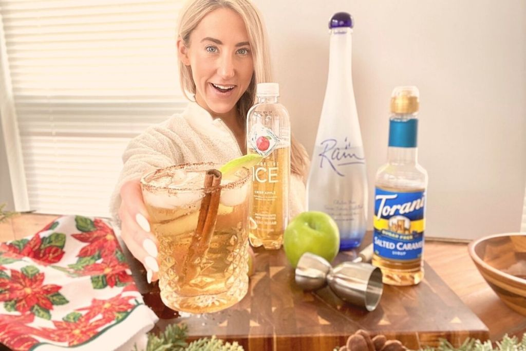 A woman holding a drink behind a bar next to drink ingredients